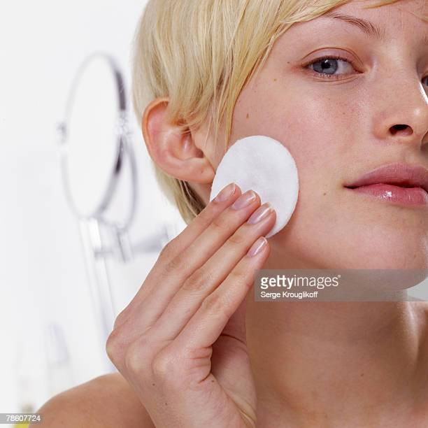 Woman removing make-up with cotton pad