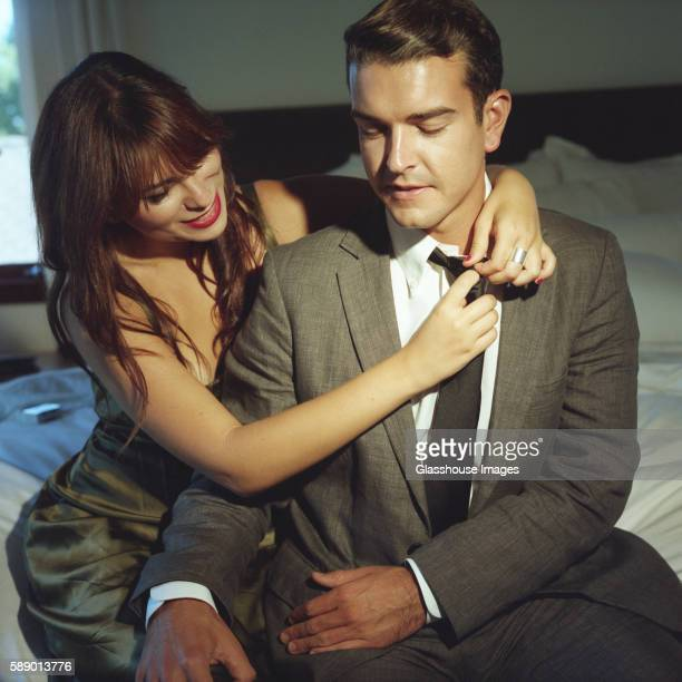 woman removing man's tie - seduction stock pictures, royalty-free photos & images
