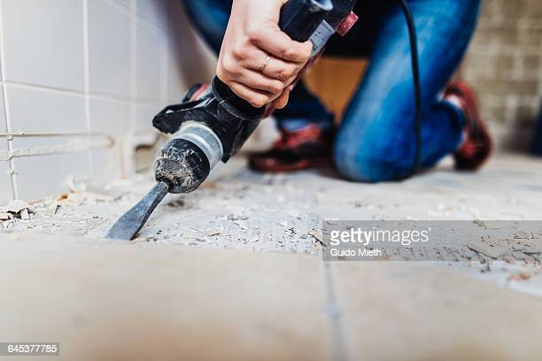 woman removing old tiles. - demolishing stock pictures, royalty-free photos & images
