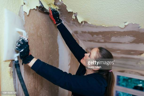 Woman removing old wall paper with hot steam.