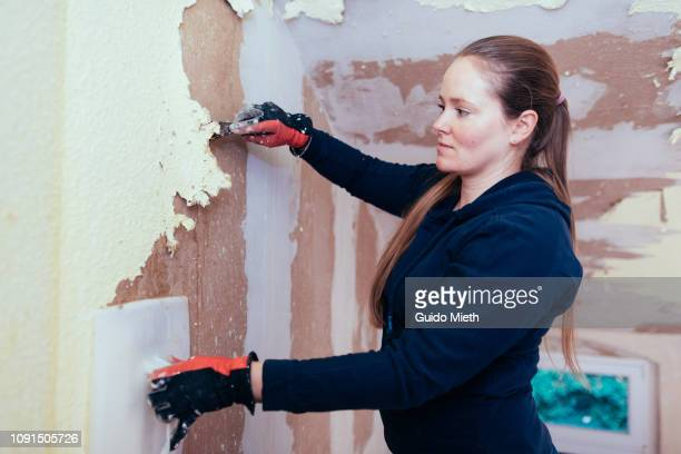 Woman removing old wall paper with spatula.