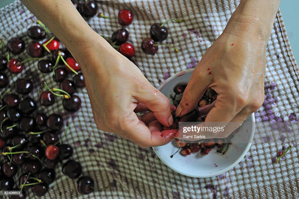 Woman removing pits from cherries : Stock Photo