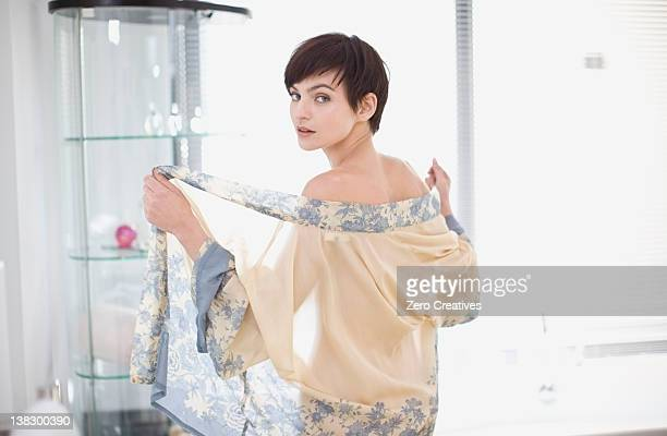 Woman removing sheer robe in bathroom