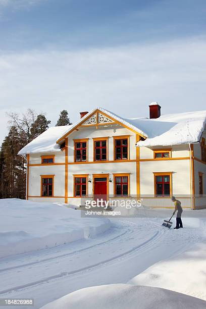 woman removing snow from driveway - snow shovel stock photos and pictures