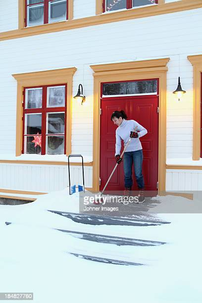 Woman removing snow from porch