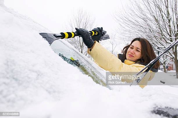 Woman Removing Snow from Windshield