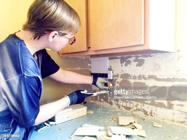 Woman Removing Tiles From Wall