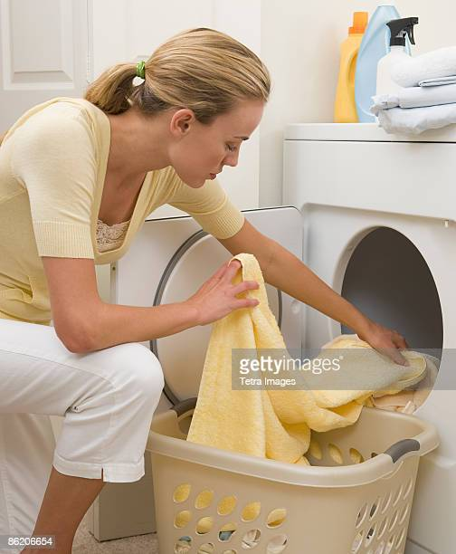 Woman removing towels from dryer