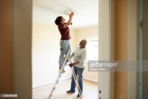 woman renovating home with father - adjusting stock pictures, royalty-free photos & images