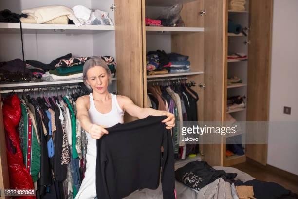 vrouw die haar garderobe in haar slaapkamer reorganiseert - keurig stockfoto's en -beelden