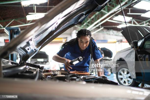 woman repairing a car in auto repair shop - mechanic stock pictures, royalty-free photos & images
