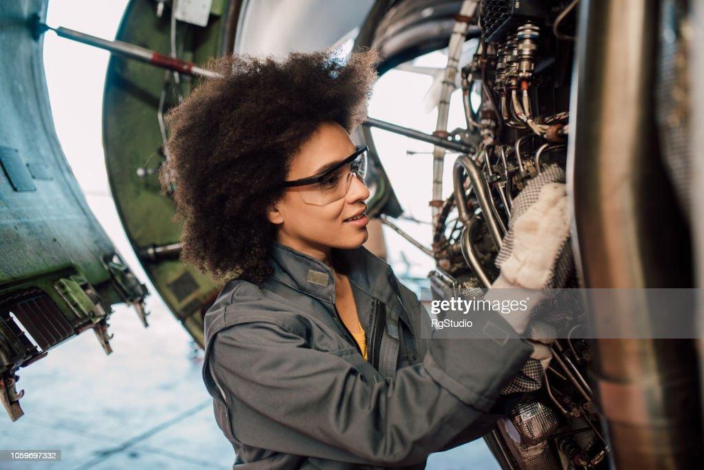 Woman repairing an aircraft : Stock Photo