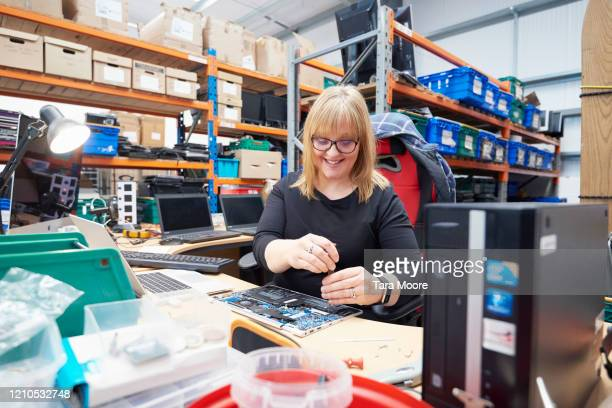 woman repairing computer in recycling centre - femalefocuscollection stock pictures, royalty-free photos & images
