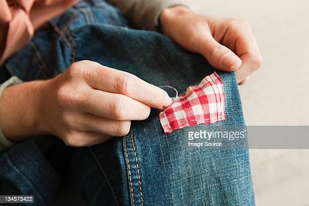 Woman repairing jeans, close up