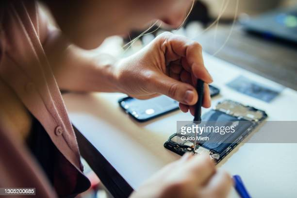 woman repairing mobile phone at home, changing damaged part. - repairing stock pictures, royalty-free photos & images