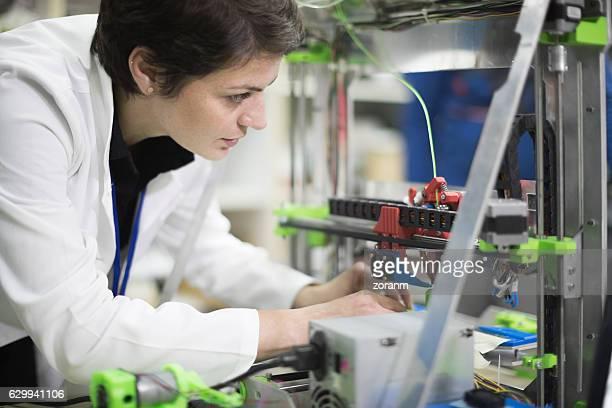 Woman repairinga 3D printer