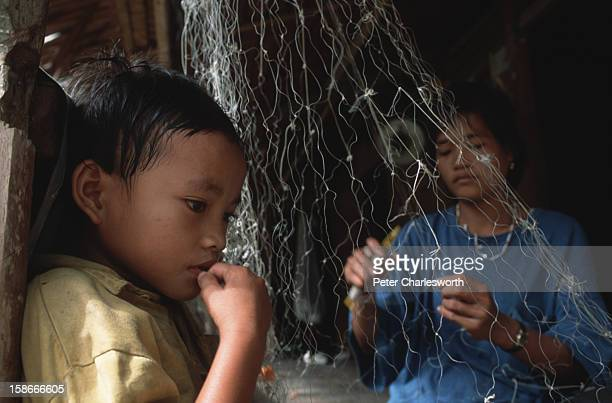 A woman repairs fishing nets as she sits with her son in the front of her primitive wood house The culture in the Mentawai Islands is based on...