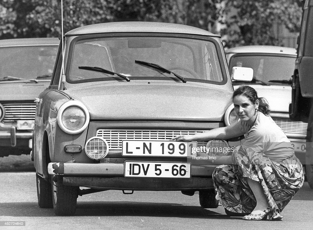 Woman replacing her old GDR license plate by a new one, which matches the license plates of the German Federal Republic on September 07, 1990, in Leipzig, Germany. The year 2014 marks the 25th anniversary of the fall of the Berlin Wall.