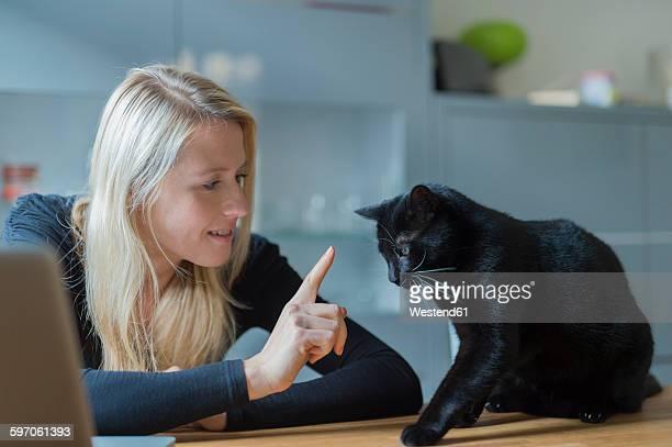 woman reproving her cat sitting on dining table - alleen één mid volwassen vrouw stockfoto's en -beelden