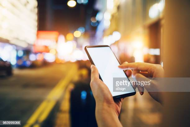 woman requesting a ride with smartphone in downtown city street at night - lyft stock photos and pictures