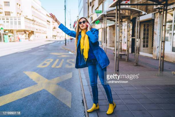 woman requesting a taxi while talking on the phone - catching stock pictures, royalty-free photos & images