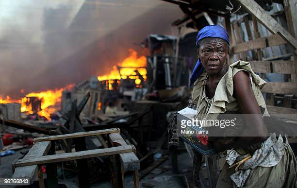 Woman rescues goods including a chicken from an approaching fire in the Iron Market area January 29, 2010 in Port-au-Prince, Haiti. Multiple...
