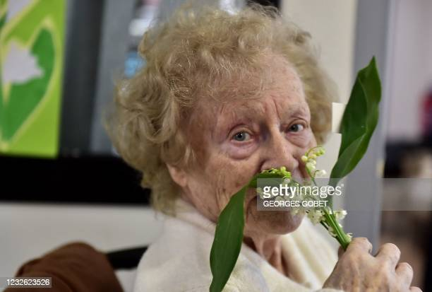 Woman resident of the Henri IV retirement home smells at a sprig of Lily of the Valley or Muguet offered to her by a member of staff in Toulouse,...