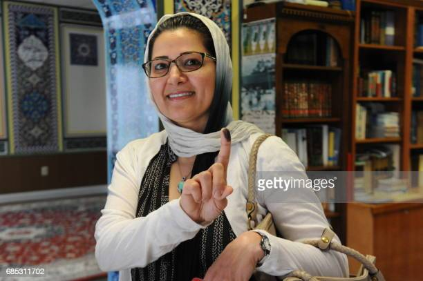 A woman residing in the US shows ink on her finger after casting her vote for the Iran Presidential election on May 19 2017 at a polling station at...