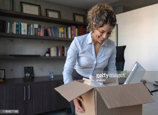 woman resigning her job and packing her belongings in a box at the office - quitting a job stock pictures, royalty-free photos & images