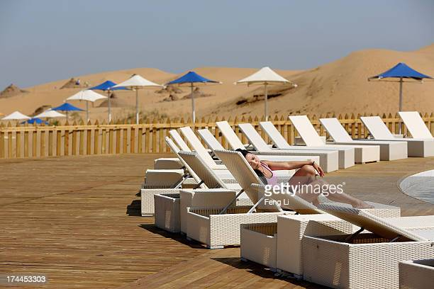 A woman rest beside a swimming pool in Xiangshawan Desert also called Sounding Sand Desert on July 20 2013 in Ordos of Inner Mongolia Autonomous...