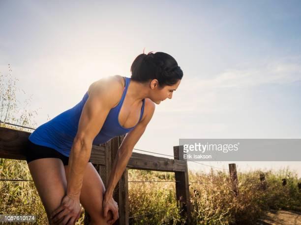 woman resting after exercise - bend over cleavage stock photos and pictures