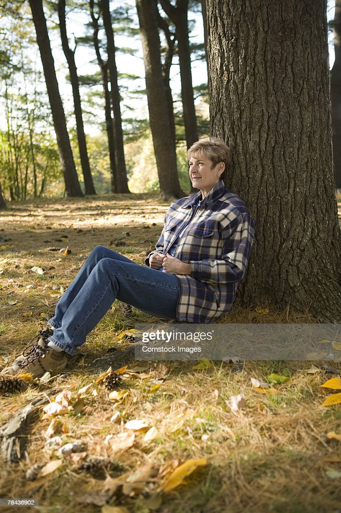 Woman resting against tree : Stockfoto
