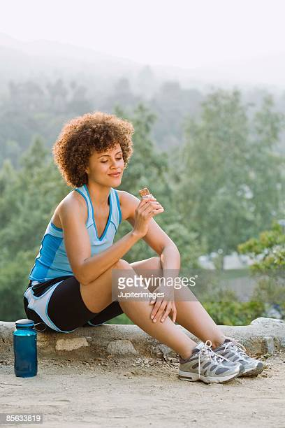 Woman resting and eating a granola bar