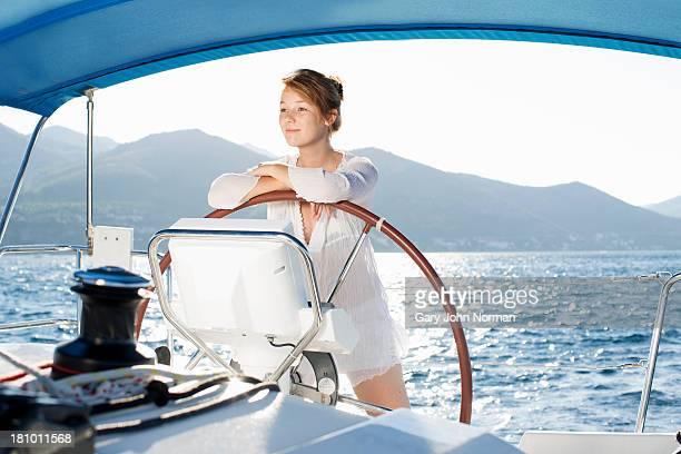 woman resting arms on wheel of sailing yacht