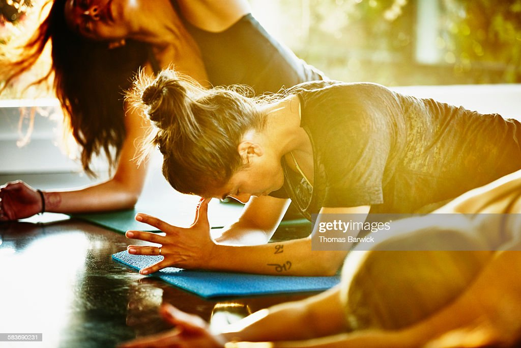 Woman resting between poses in yoga class : Stock Photo