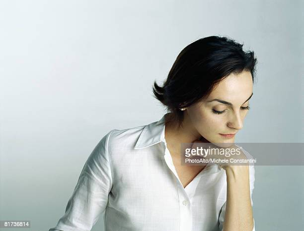 woman resting chin on hand, looking down, portrait - medium shot stock pictures, royalty-free photos & images