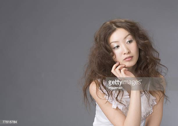 woman resting chin on hand - permed hair stock photos and pictures