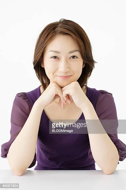 woman resting chin on hands, studio shot - 顎に手をやる ストックフォトと画像
