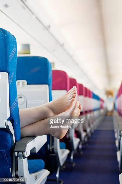 woman resting feet on seat armrest of commercial airplane - barefoot stock pictures, royalty-free photos & images