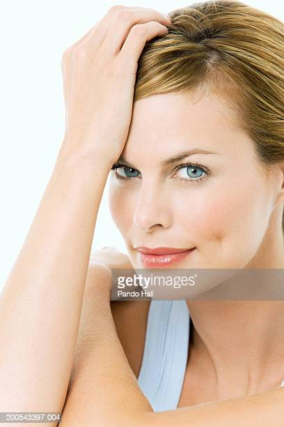 Woman resting hand on head, close-up, portrait