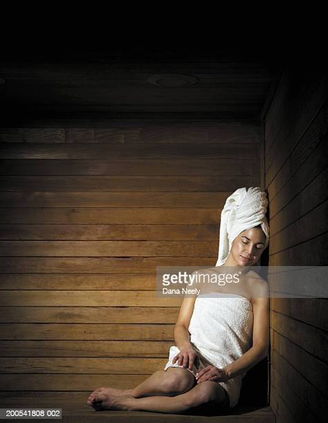 Woman resting head against wall in sauna, eyes closed