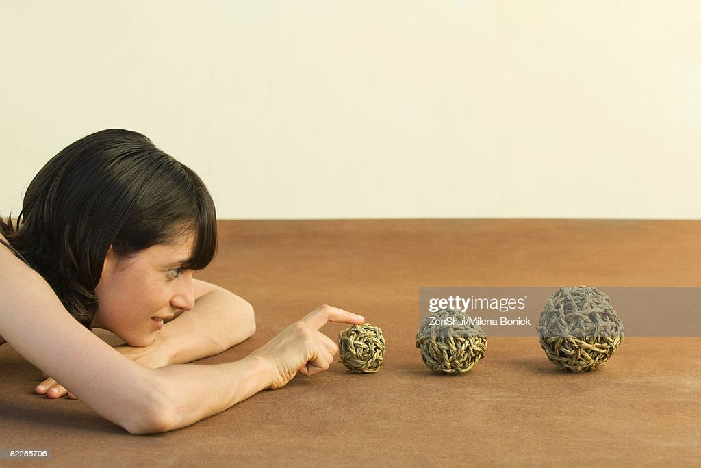 Woman resting head on arms, looking at balls of string, side view : Stock Photo