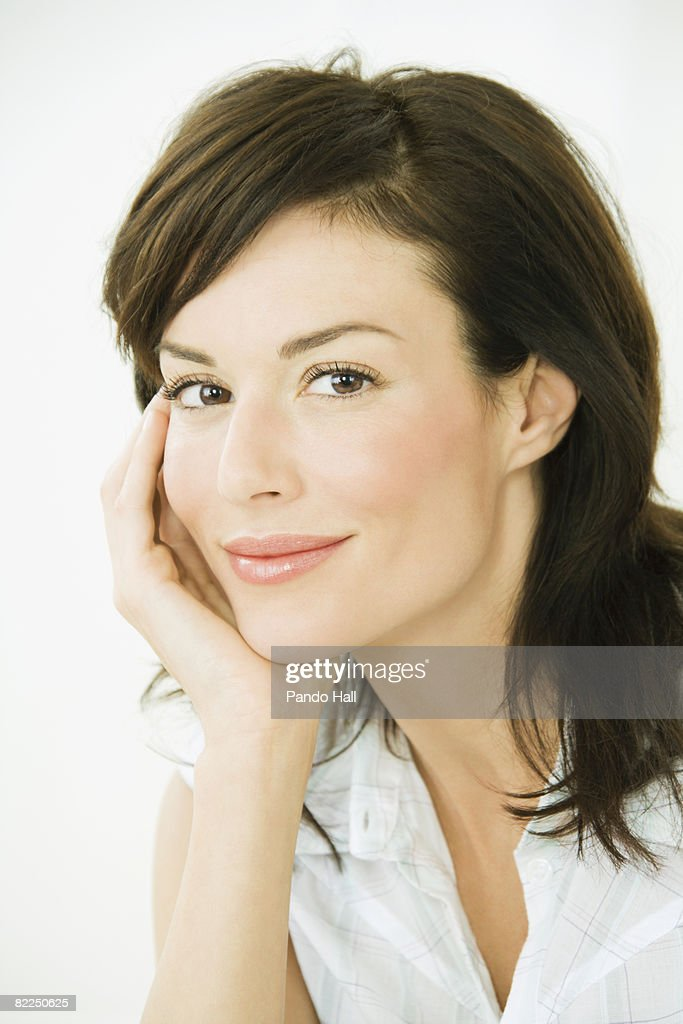 Woman resting head on hand, smiling, portrait : Stock Photo