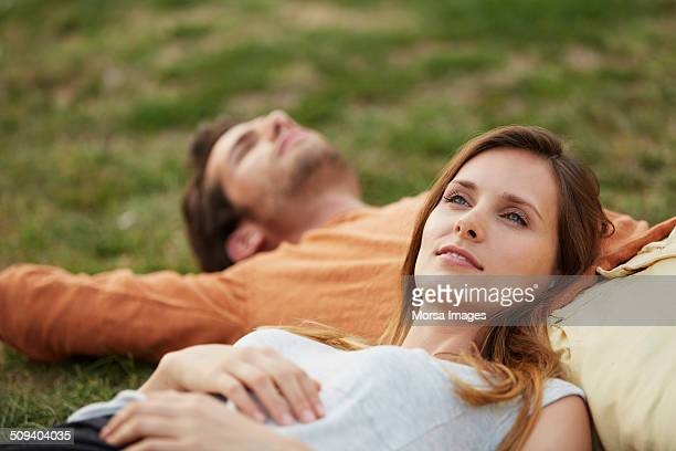 Woman resting head on man's stomach at park