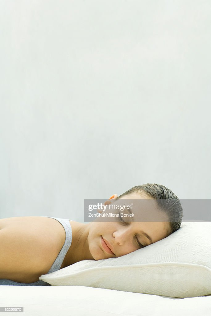 Woman resting head on pillow, eyes closed : Stock Photo