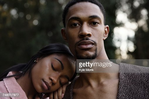 Woman resting head on shoulder of man
