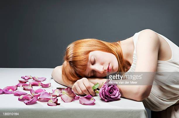 Woman resting head on table, holding rose.