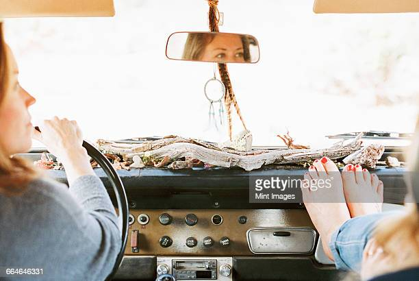 A woman resting her bare feet on the dashboard of a 4x4, on a road trip with another woman driving.