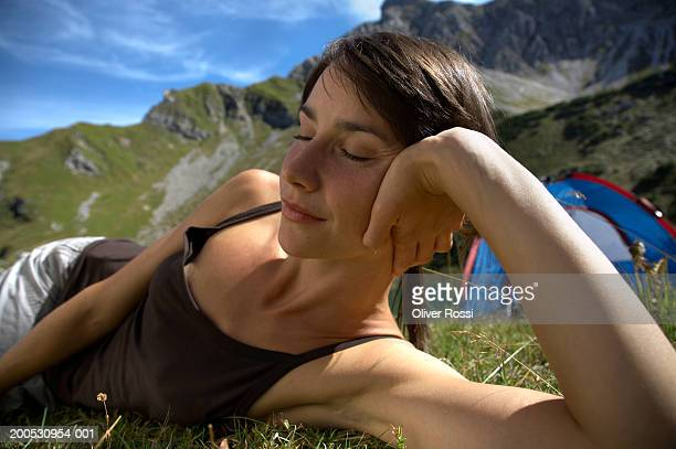 Woman resting in mountainous landscape, eyes closed