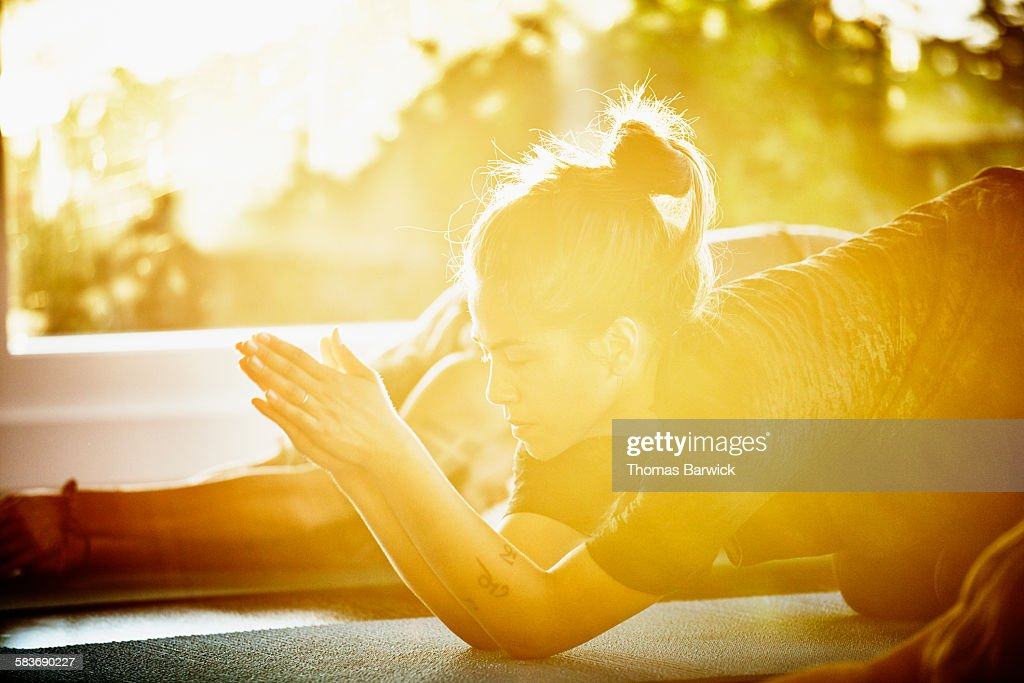 Woman resting in prayer position between poses during yoga class in studio